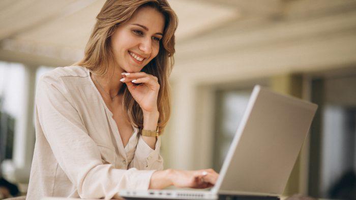 Mulher sentada de frente para o seu computador enquanto trabalha sorrindo.