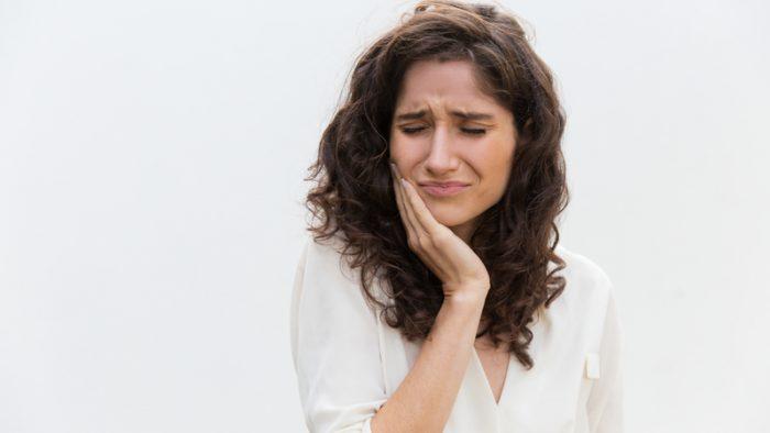 Mulher com a mão no rosto expressando a dor no dente.