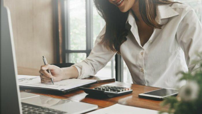 Mulher sentada à mesa, com vários papéis e notebook fazendo home office.